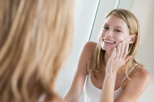 Woman in bathroom applying face cream smiling